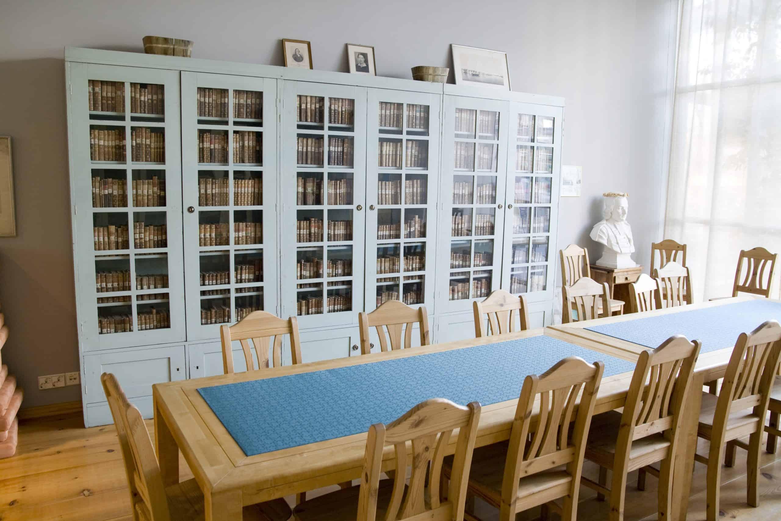 Lukuseuran huoneessa on vihreä kaappi, jossa vanhoja kirjoja. Huoneessa on myös pitkä pöytä ja tuolit.
