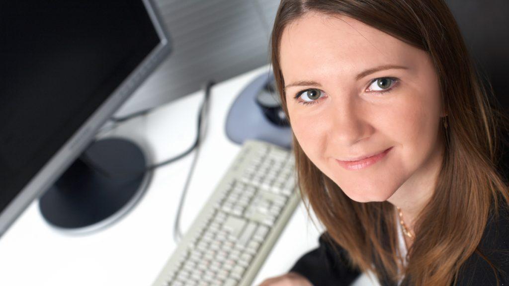Nainen katsoo kuvaajaa, taustalla tietokone