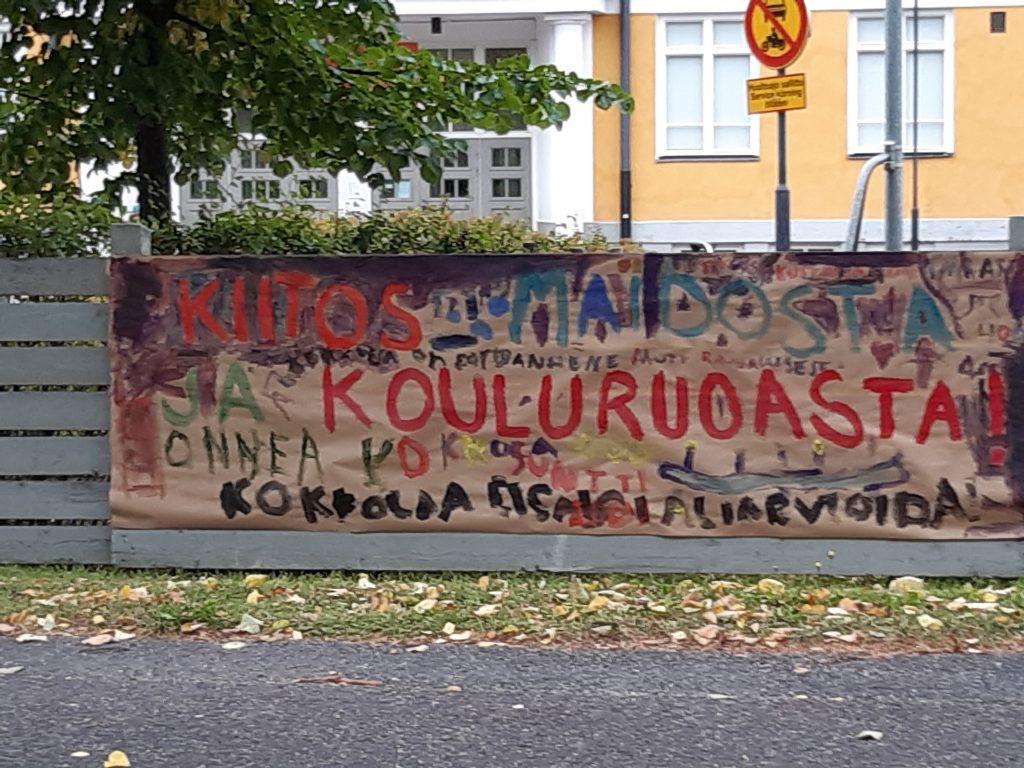 Koulun edessä lasten piirtämä kyltti, jossa lukee kiitos kouluruoasta