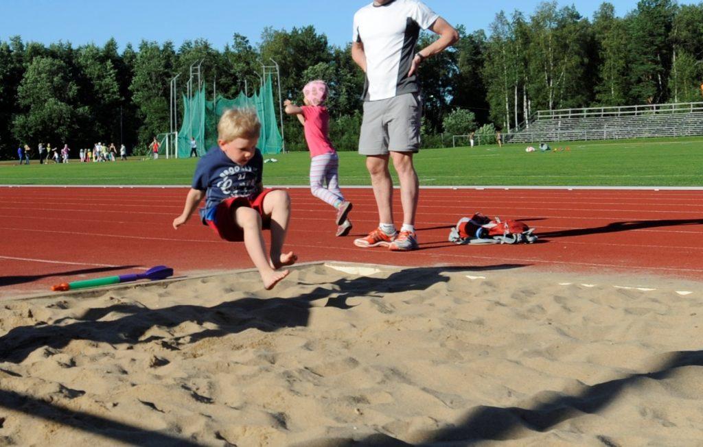 Kuvassa pieni lapsi urheilukentällä hyppäämässä pituutta