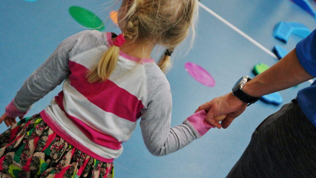 Lapsi liikuntahallissa käsi kädessä aikuisen kanssa