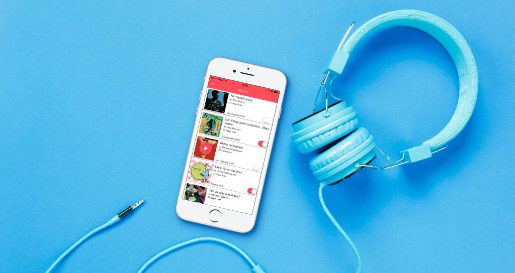 Kuvassa sinisellä taustalla älypuhelin ja kuulokkeet