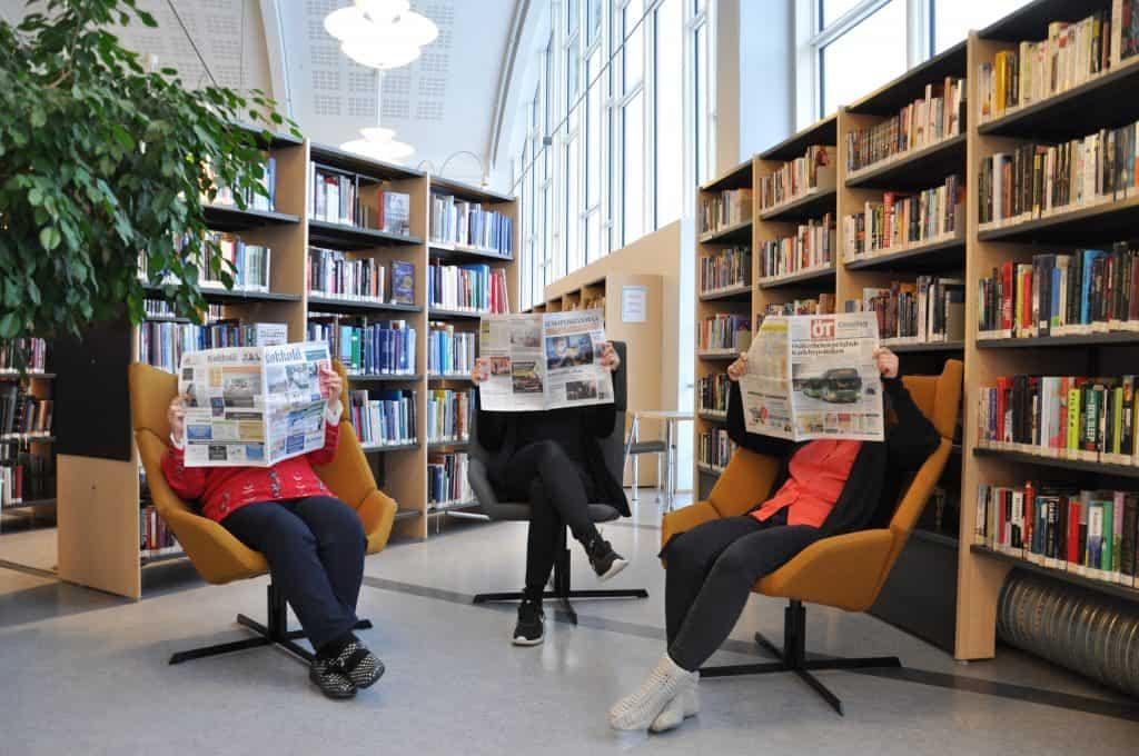 Lehdenlukijoita kirjaston hyllyjen edessä.