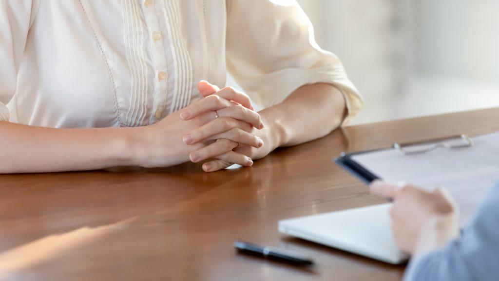 Henkilö haastattelee toista, lähikuva käsistä ja pöydästä