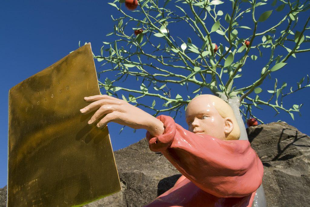 Patsas: Poika lukee kirjaa kiven päällä