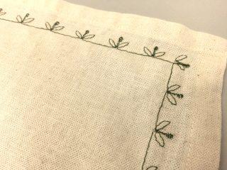 Kukkakuvio konekirjottuna kiertää valkoista liinaa.