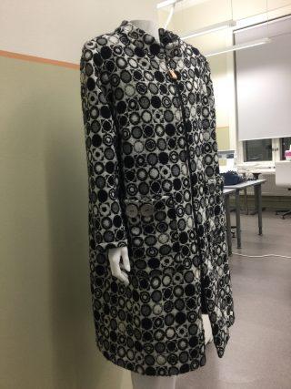 Mustavalkoisesta villakankaasta tehty polvipituinen takki.