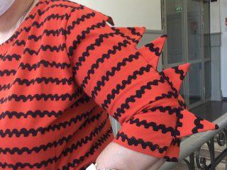 Naisen trikoopusero, jossa hihoissa kolmiokoristelu.