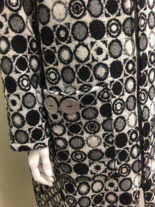 Mustavalkoisesta villakankaasta ommellun takin taskun yksityiskohta.