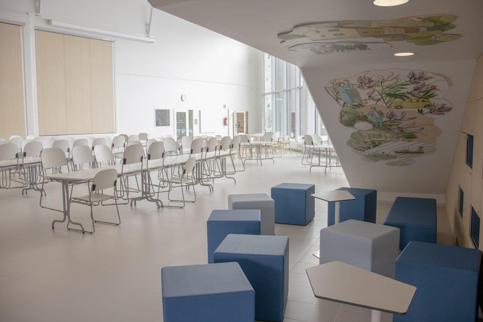 Kuvassa näkyy koulun ruokala, jossa on pöytiä ja tuoleja.