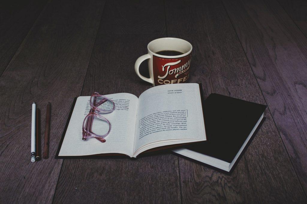 kahvikupin edessä kirjoja ja kirjan päällä silmälasit.
