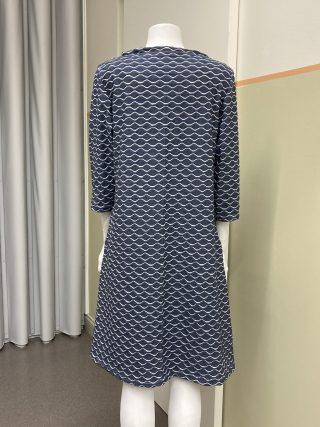 Naisen mekko, tummansinisellä pohjalla valkoisia aaltokuvioita. Kuva takaa.