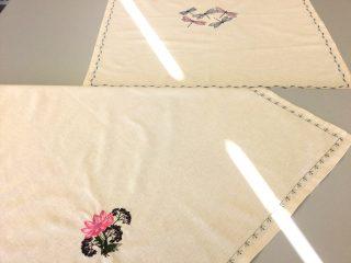 Kaksi valkoista liinaa, joista toisessa konekirjottu kukka ja toisessa konekirjotut sudenkorennot.