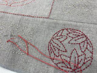 Borokirjailua pellavakankaalle punaisella langalla.