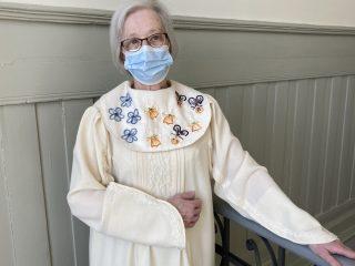 Nainen valkoisessa, käsinkirjaillussa pitkässä puvussa.