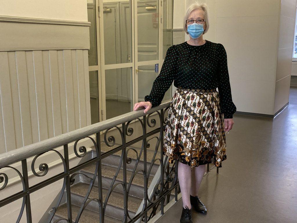 Nainen; pilkullinen pusero ja kuviollinen hame.