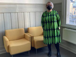 Naisen yllä vihreäkuvioinen trikoomekko.