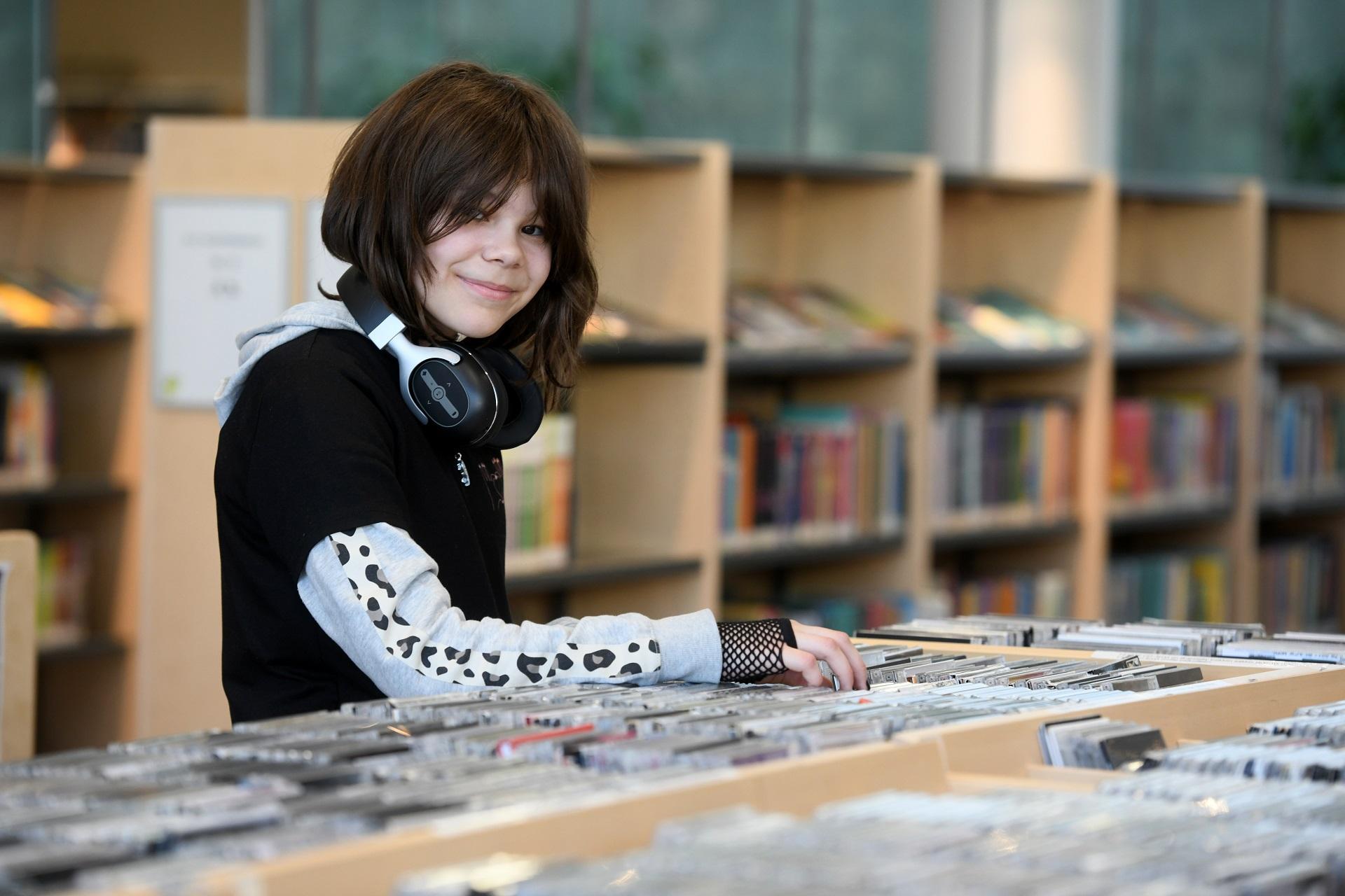 Nuori tyttö selailee kirjastossa cd-levyjä.