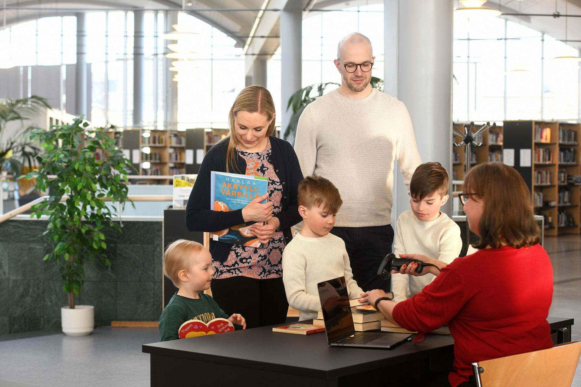 Kaksi aikuista ja kolme lasta lainaamassa kirjoja kirjastossa. Kirjastovirkailija istuu tiskin takana ja lainaa kirjat.