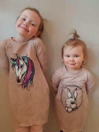 kaksi tyttöjen trikoomekkoa eläinaiheisilla painetuilla kuvilla.