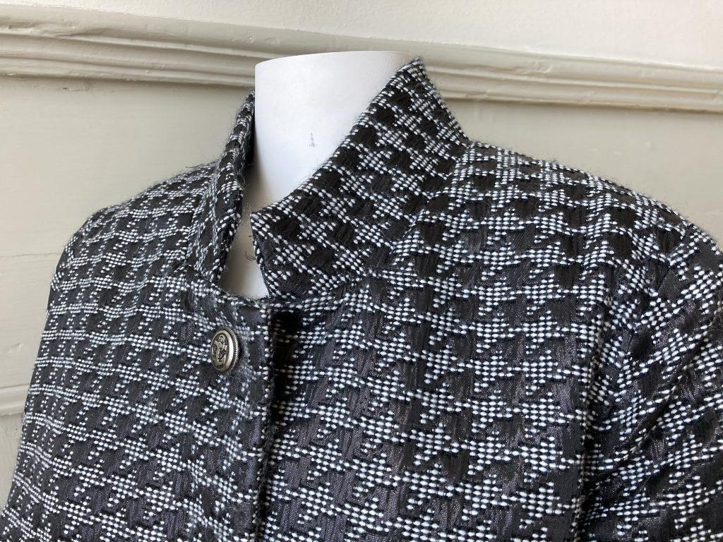 Naisen mustavalkoinen takki., yksityiskohta kauluksesta.