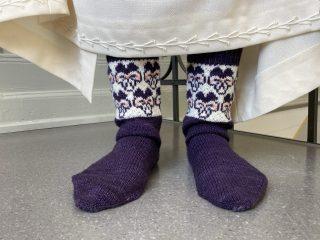 Naisen jalassa käsinneulotut, orvokkikuviolliset sukat.