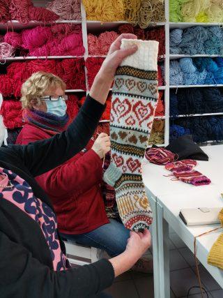 Etualalla nainen esittelee neulomiaan kirjoneulevillasukkia, taka-alalla erivärisiä neulelankoja.