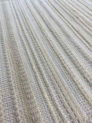 Vaaleansävyinen matto, jossa kohoraitoja.