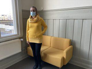 Nainen yllään trikoohuppari keltainen.