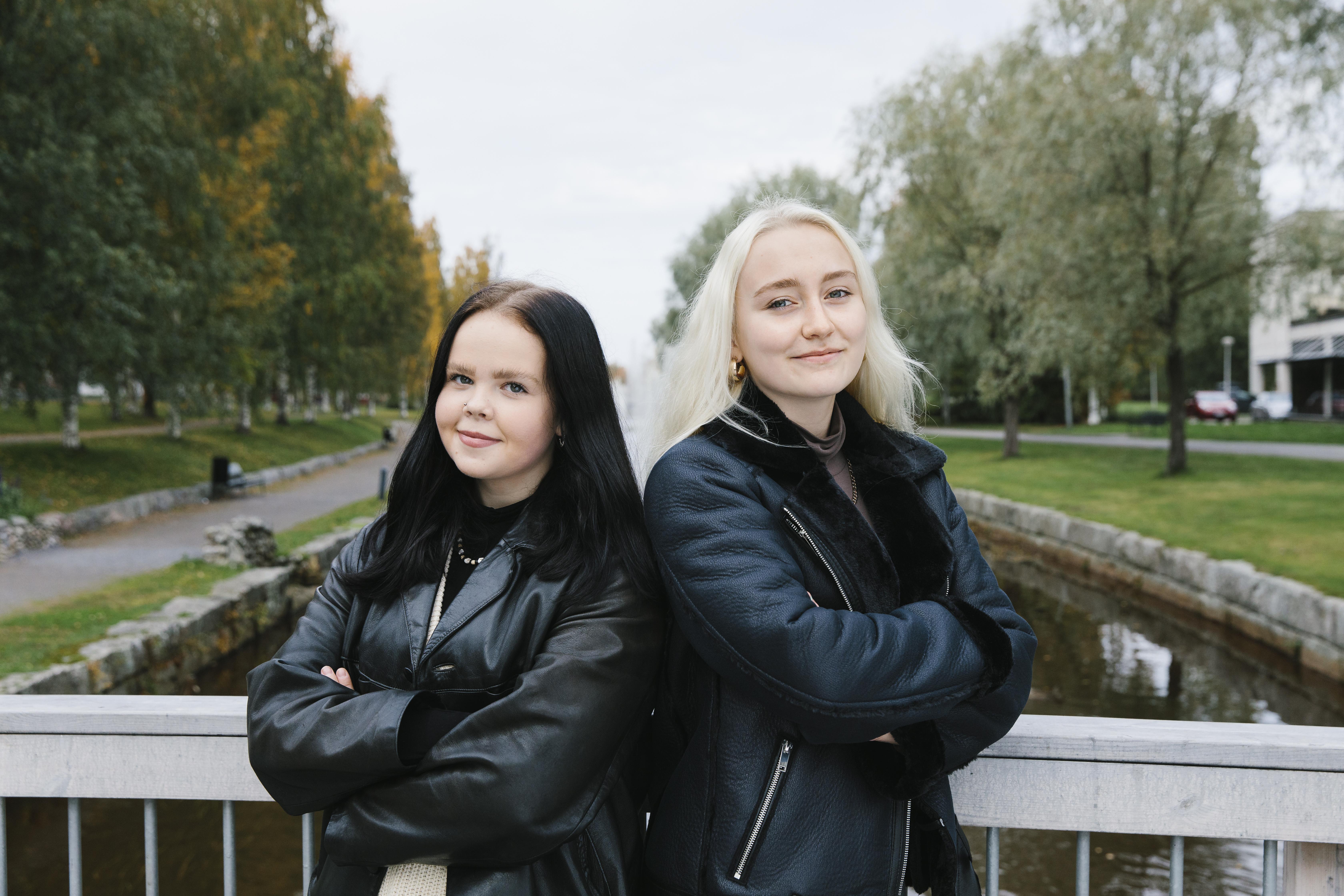 Kaksi tyttöä seisoo Suntin varrella ja katsoo kameraan