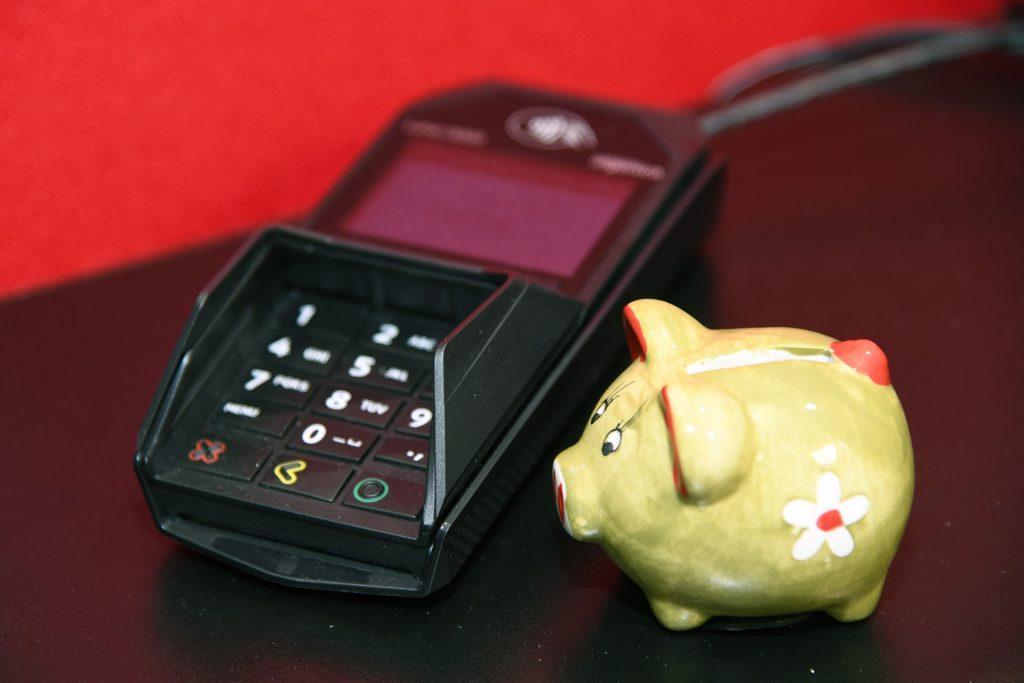 Korttimaksupääte ja keltainen säästöpossu.