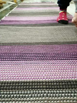 Vihreä-violettiraitainen matto.