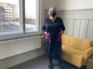 Nainen esittelee mustaa pellavamekkoa käsinkuvioiduilla taskuilla.