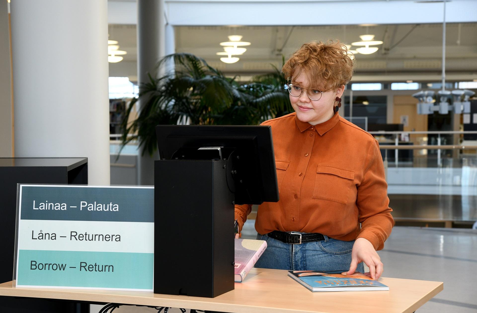 En ung kvinna lånar böcker vid en låneautomat.