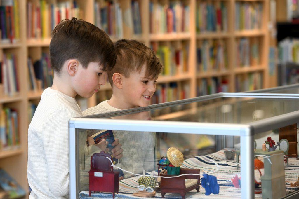 Kaksi nuorta poikaa katselee vitriinin sisältöä. Vitriinissä on pieniä nukkekodin esineitä.
