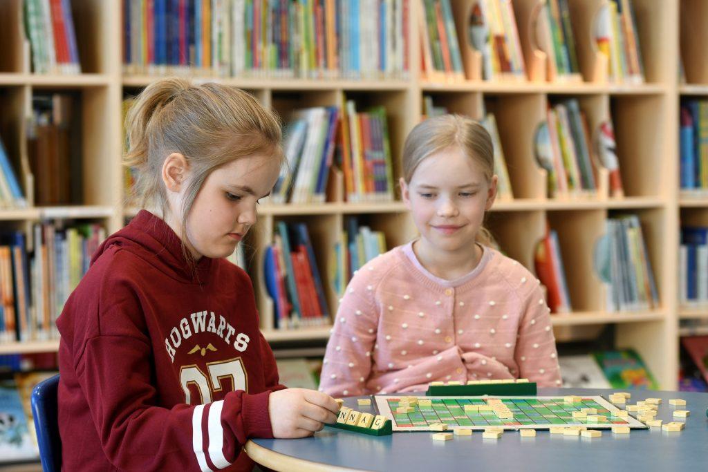 Kaksi nuorta työttöä pelaa Scrabble-sanapeliä.