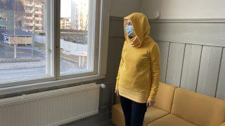 Nainen esittelee keltaista trikoohupparia.