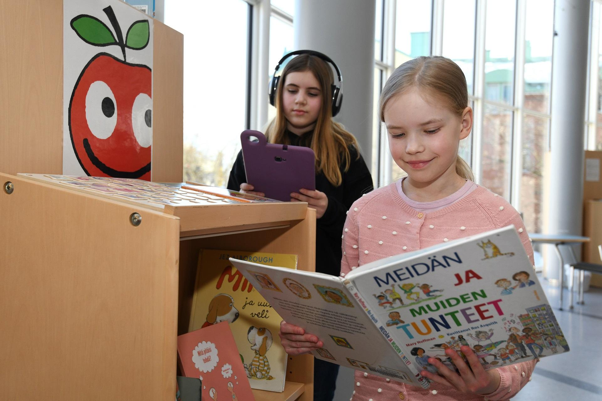 Kaksi nuorta tyttöä seisovat kirjahyllyn luona. Kirjahyllyn päädyssä on ompun kuva. Toinen tytöistä lukee kirjaa ja toinen katsoo kirjaston Hublet-tablettia kuulokkeet korvillaan.