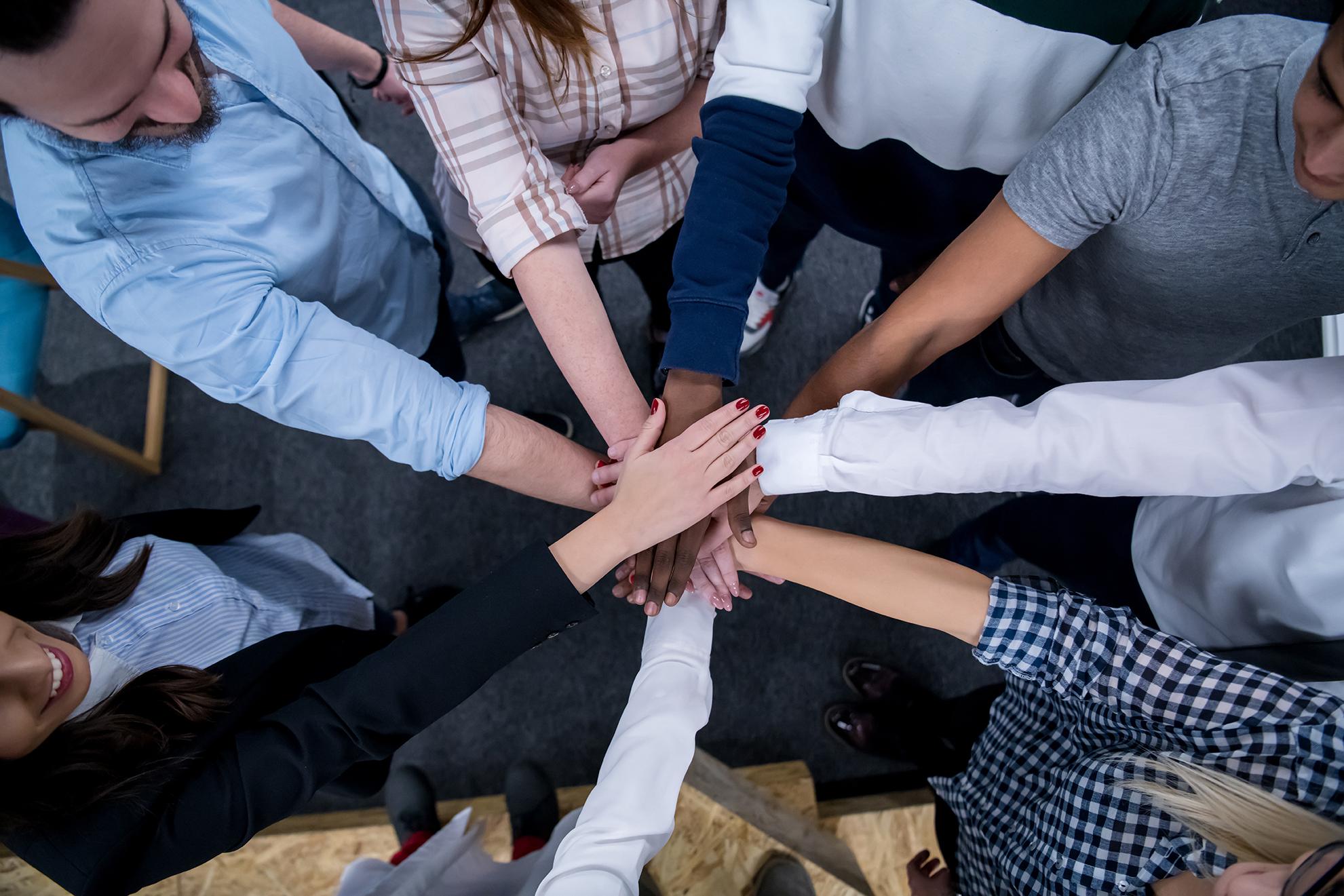 Monikulttuurinen ryhmä ihmisiä iloitsee saavutuksestaan töissä