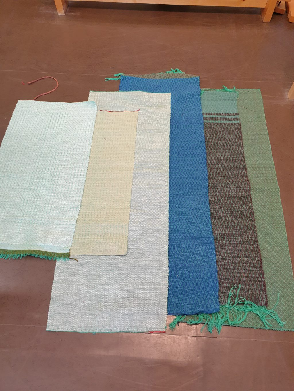 Vihreään loimeen kudottuja tekstiilejä.