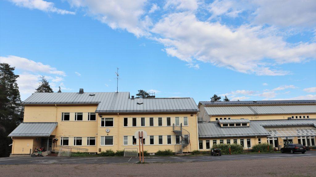 vaaleankeltainen koulu- ja monitoimitalorakennus, sininen poutapilvitaivas
