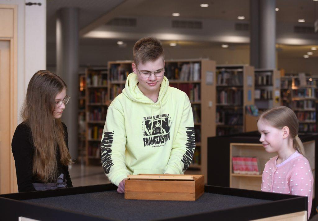 Kolme nuorta seisoo pöydän ympärillä ja pelaa Labyrintti-peliä.