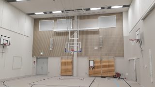 Ykspihlajan koulun liikuntasali puolapuineen ja koripallotelineineen.