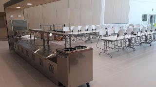 Ykspihlajan koulun tyhjillään oleva ruokala. Etualalla ruokalinjasto ja sen takana kaksi pitkää ruokapöytää ylös nostettuine tuoleineen.