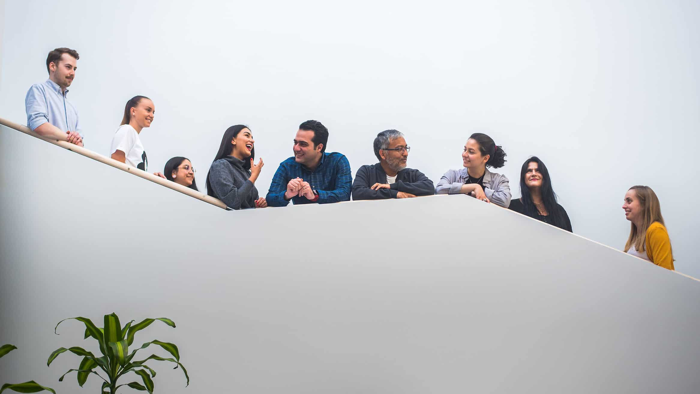 Yhdeksän nuorta kansainvälistä osaajaa nousevassa portaikossa juttelemassa iloisesti.